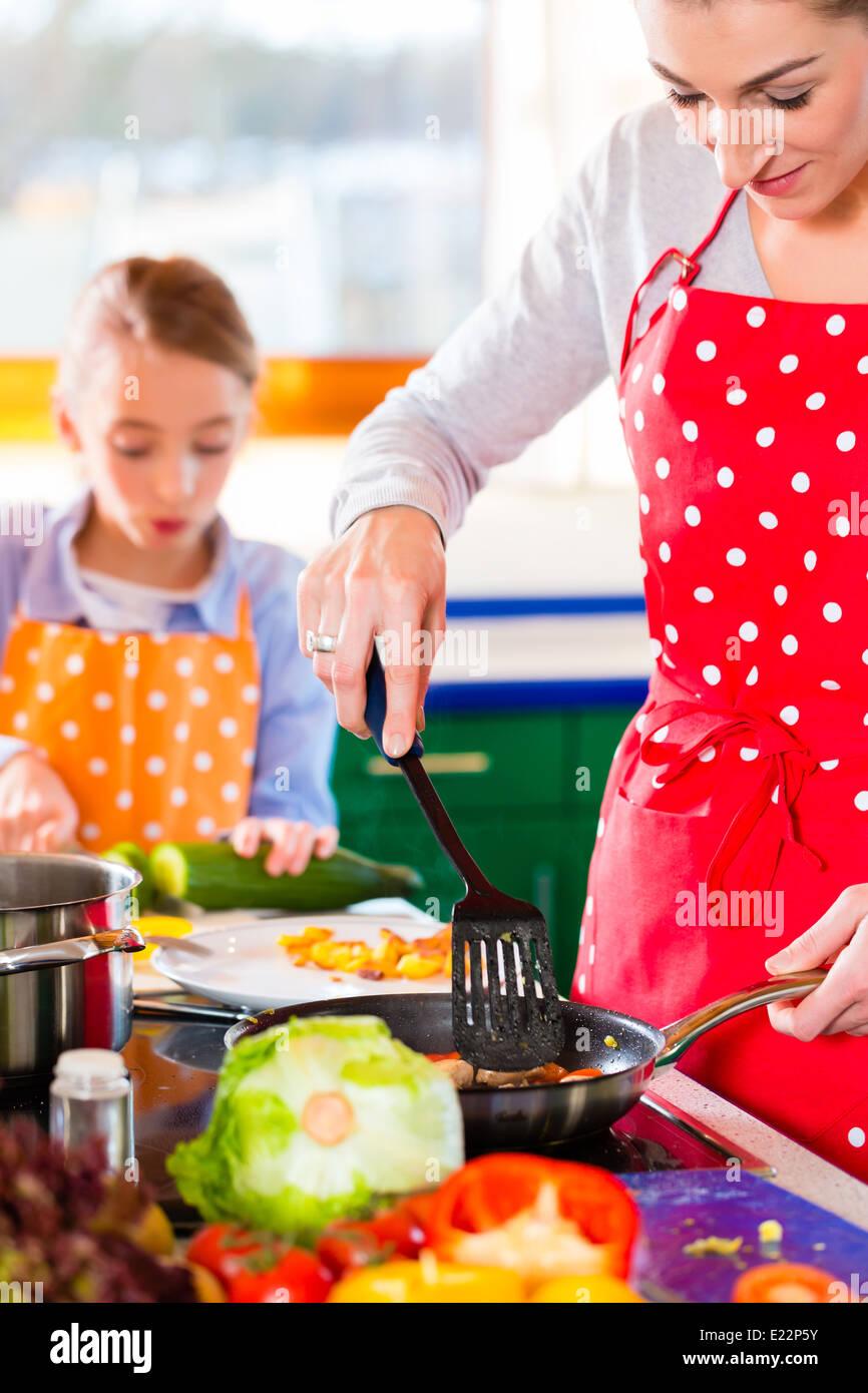 Madre Hija mostrando cómo cocinar en la cocina doméstica Imagen De Stock
