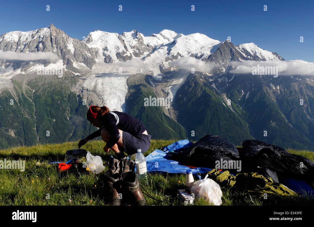 Una dama camper preparar alimentos silvestres en le Brevent acampar en los Alpes franceses con el macizo del Mont Foto de stock
