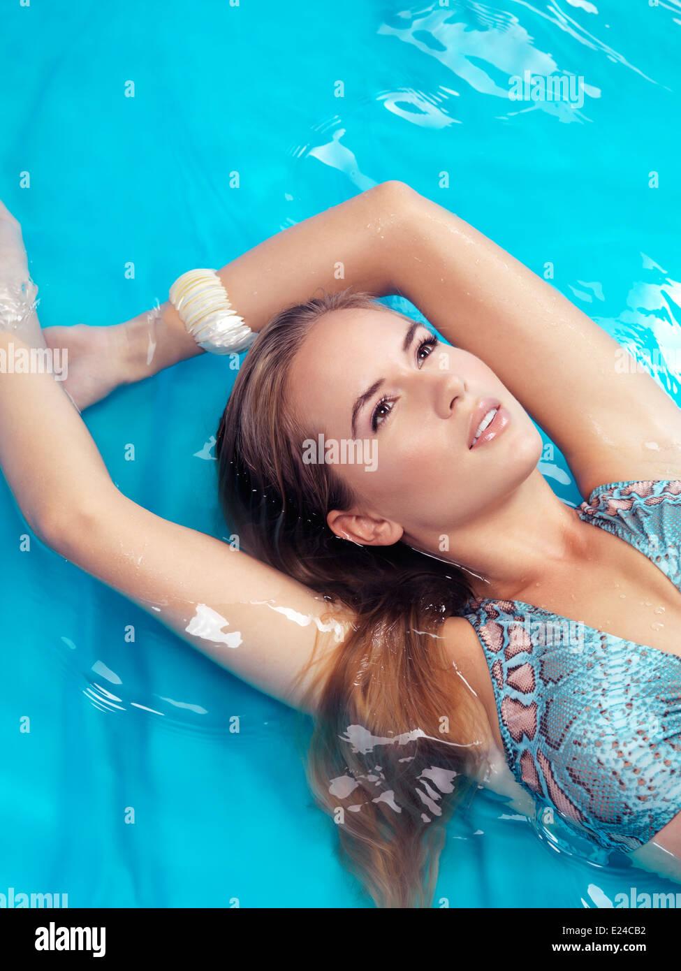 Retrato de una joven y bella mujer con cabello rubio vistiendo un traje de baño acostado en el agua azul Imagen De Stock
