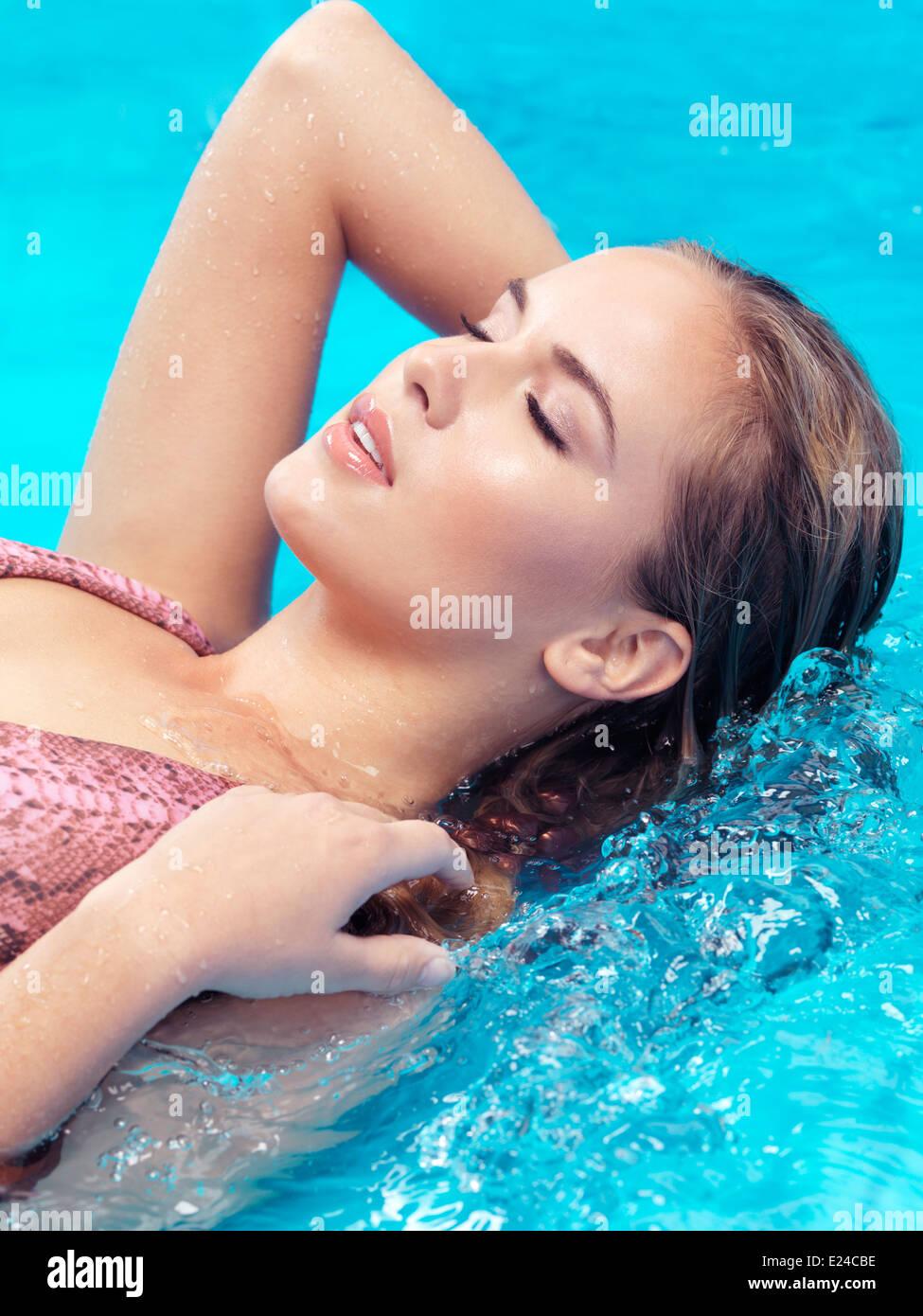 Primer plano de una bella joven rostro con ojos cerrados en agua azul Imagen De Stock
