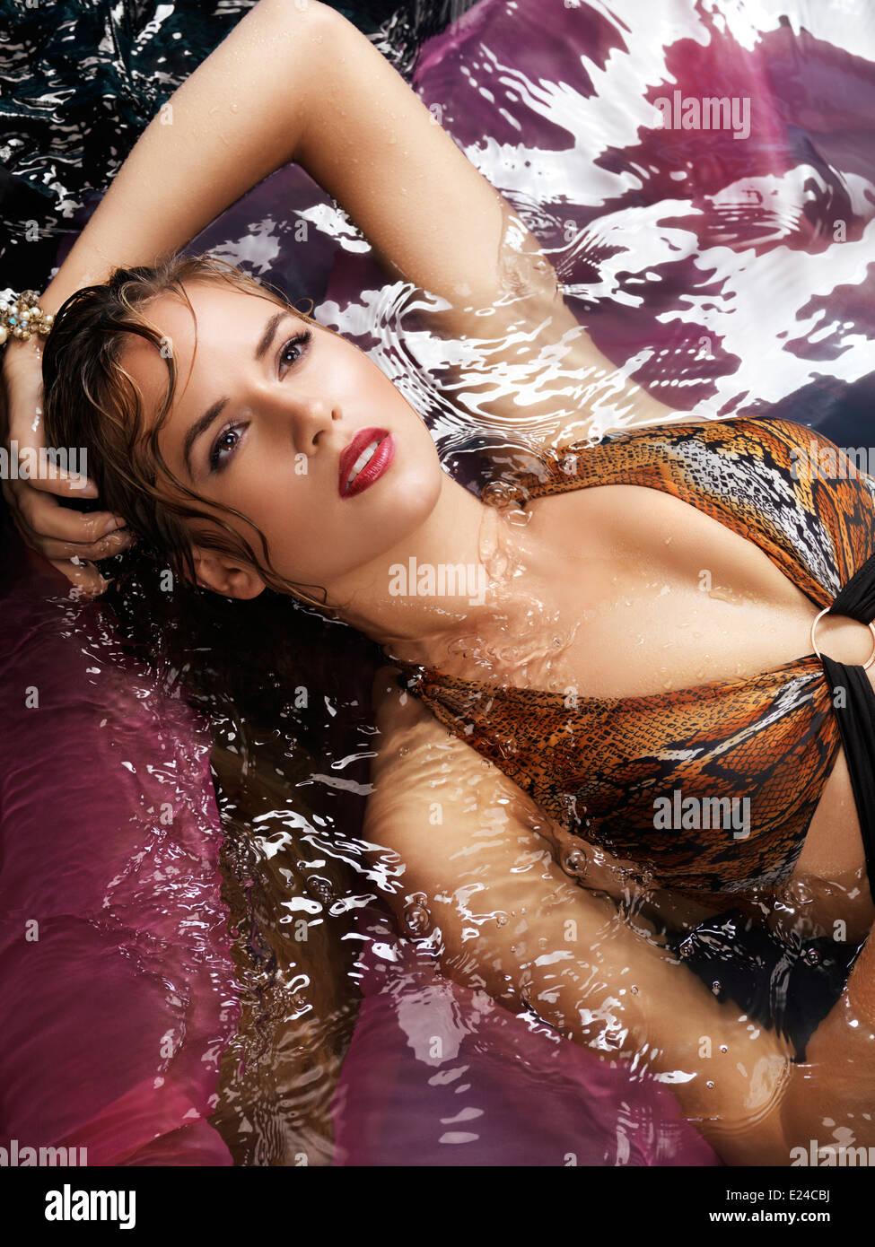 Belleza retrato de una mujer joven en un bañador tumbado en el agua Imagen De Stock