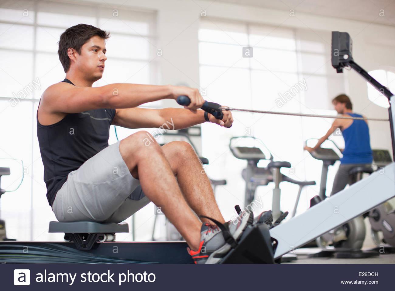 Joven el ejercicio en máquina de remo en el gymnasium Imagen De Stock