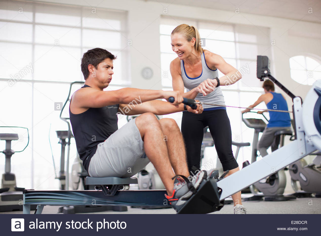 Entrenador personal con el hombre en la máquina de remo en el gymnasium Imagen De Stock