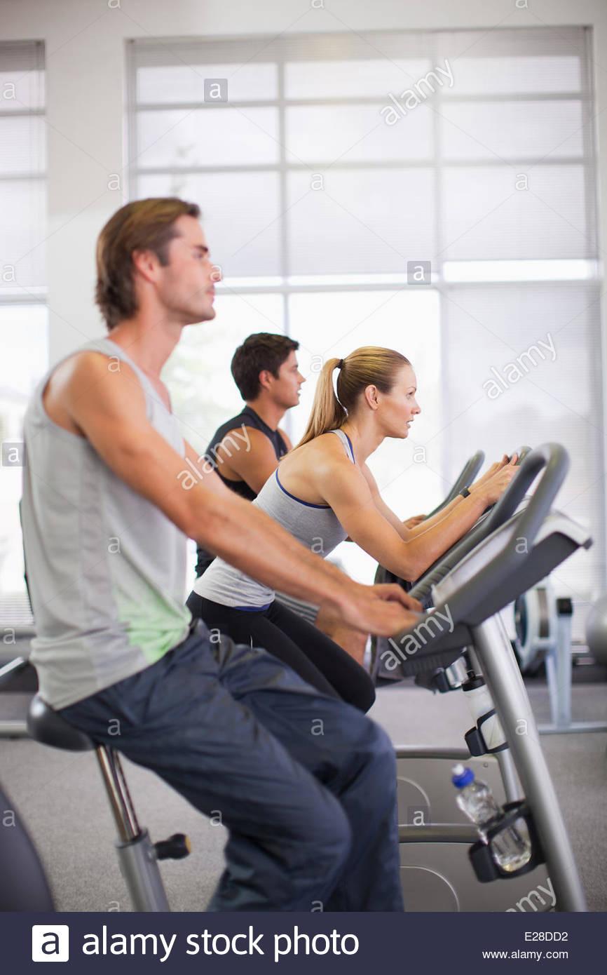 Tres personas en bicicletas de ejercicio en el gimnasio Imagen De Stock