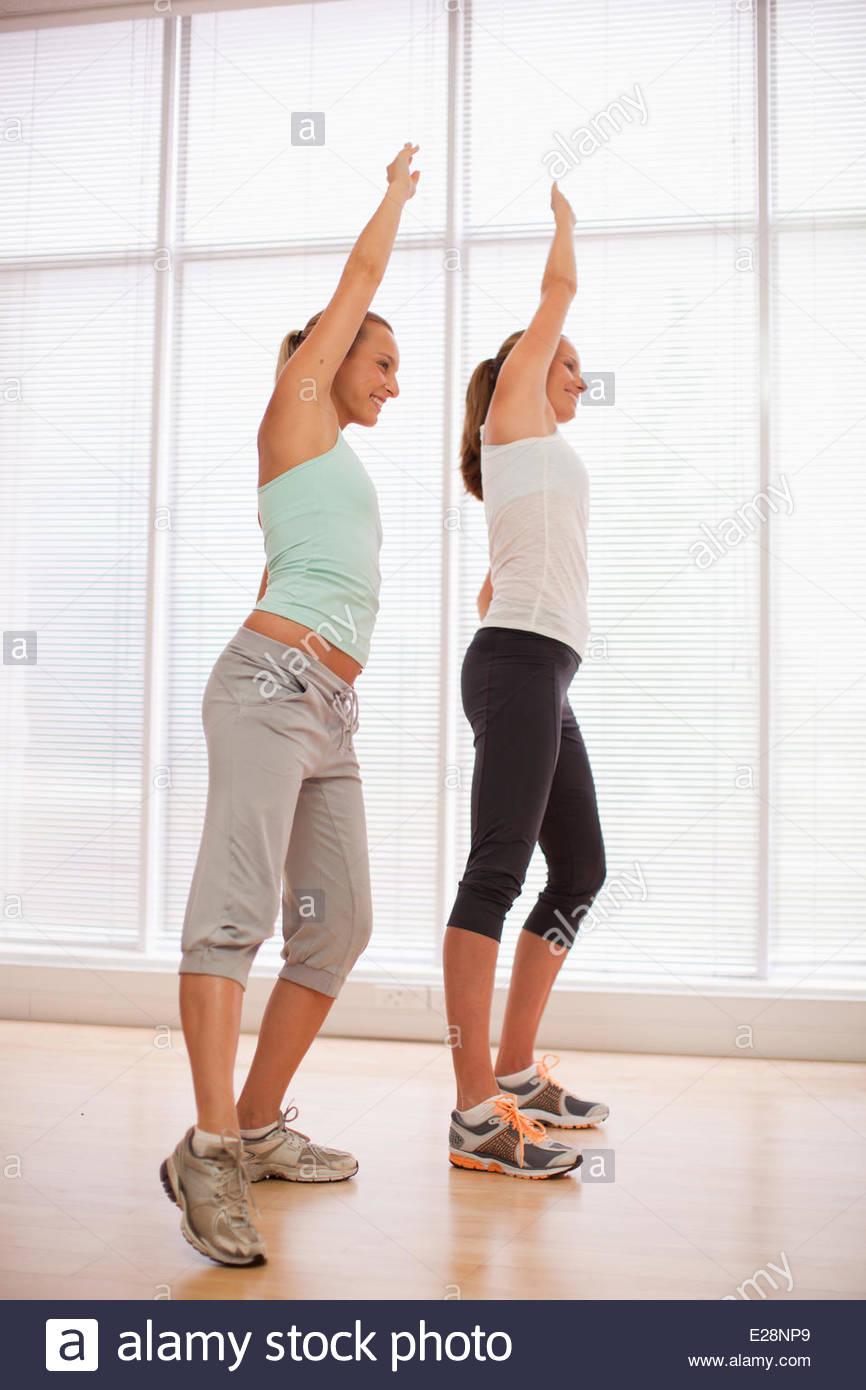 Mujer sonriente con los brazos levantados en clase de ejercicios Imagen De Stock