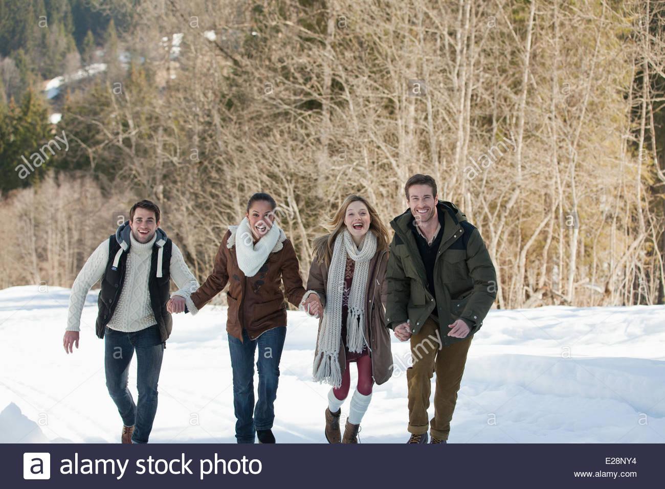 Retrato de amigos sonriente sosteniendo las manos y girando en la nieve Imagen De Stock