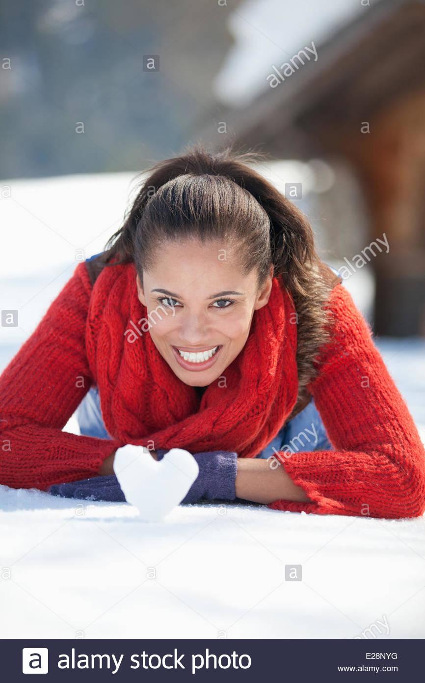 Mujer joven con bola de nieve con forma de corazón Imagen De Stock