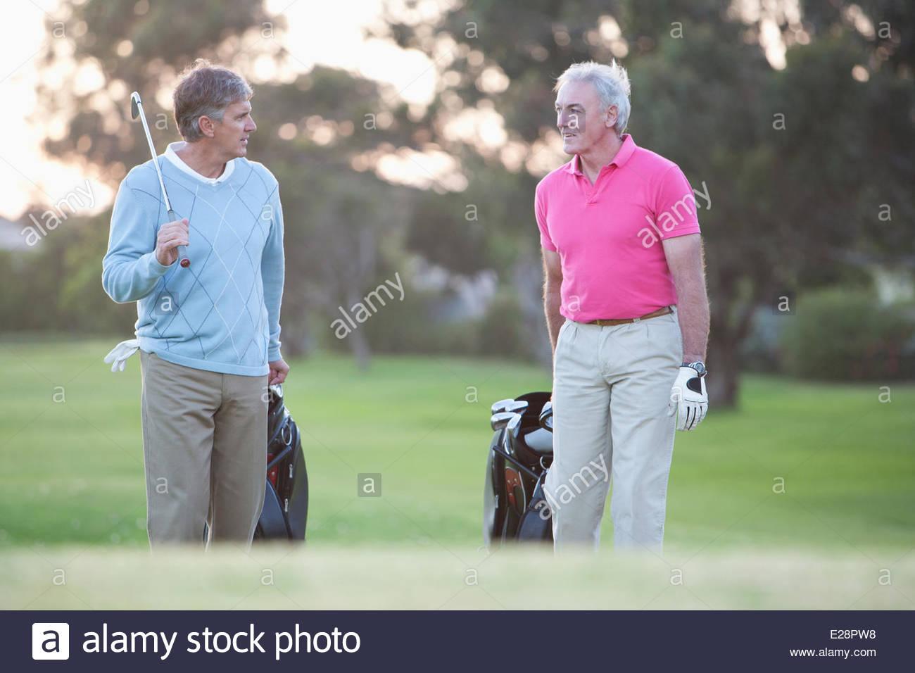 Los hombres tirando de carritos de golf Imagen De Stock
