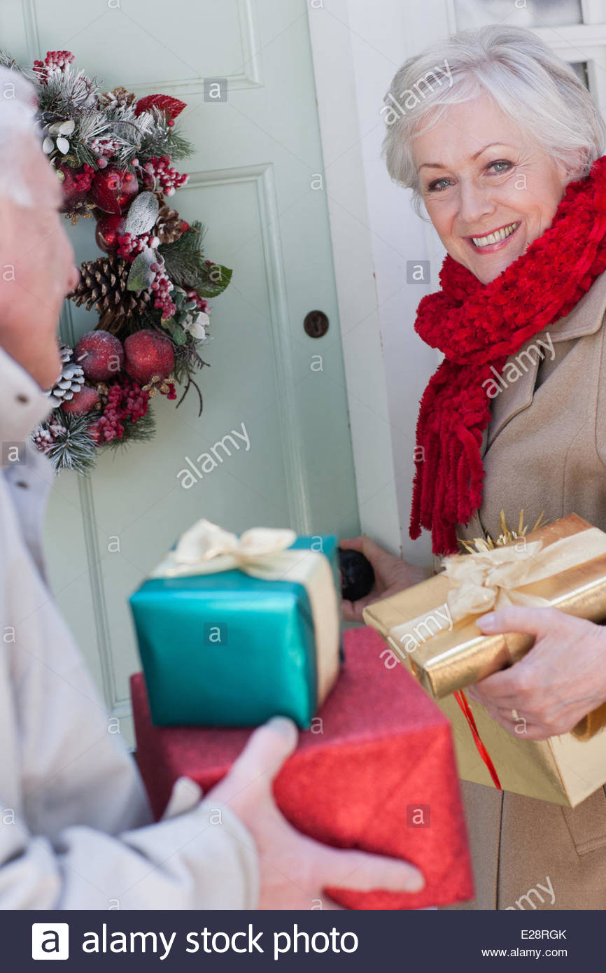 Pareja con regalos de Navidad de pie en la puerta Imagen De Stock