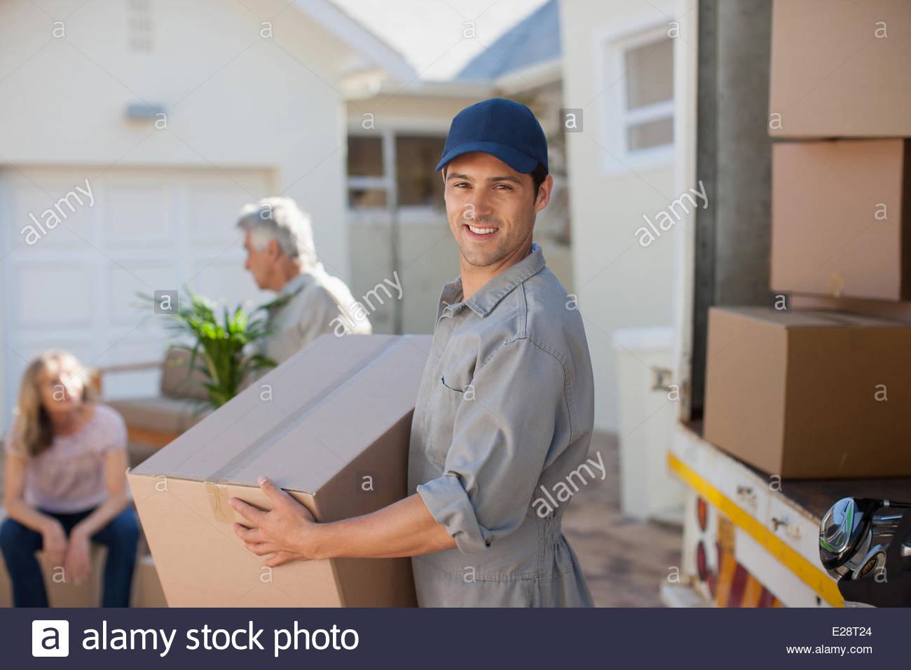El transportador ayudando pareja se muda a Nueva Casa Imagen De Stock