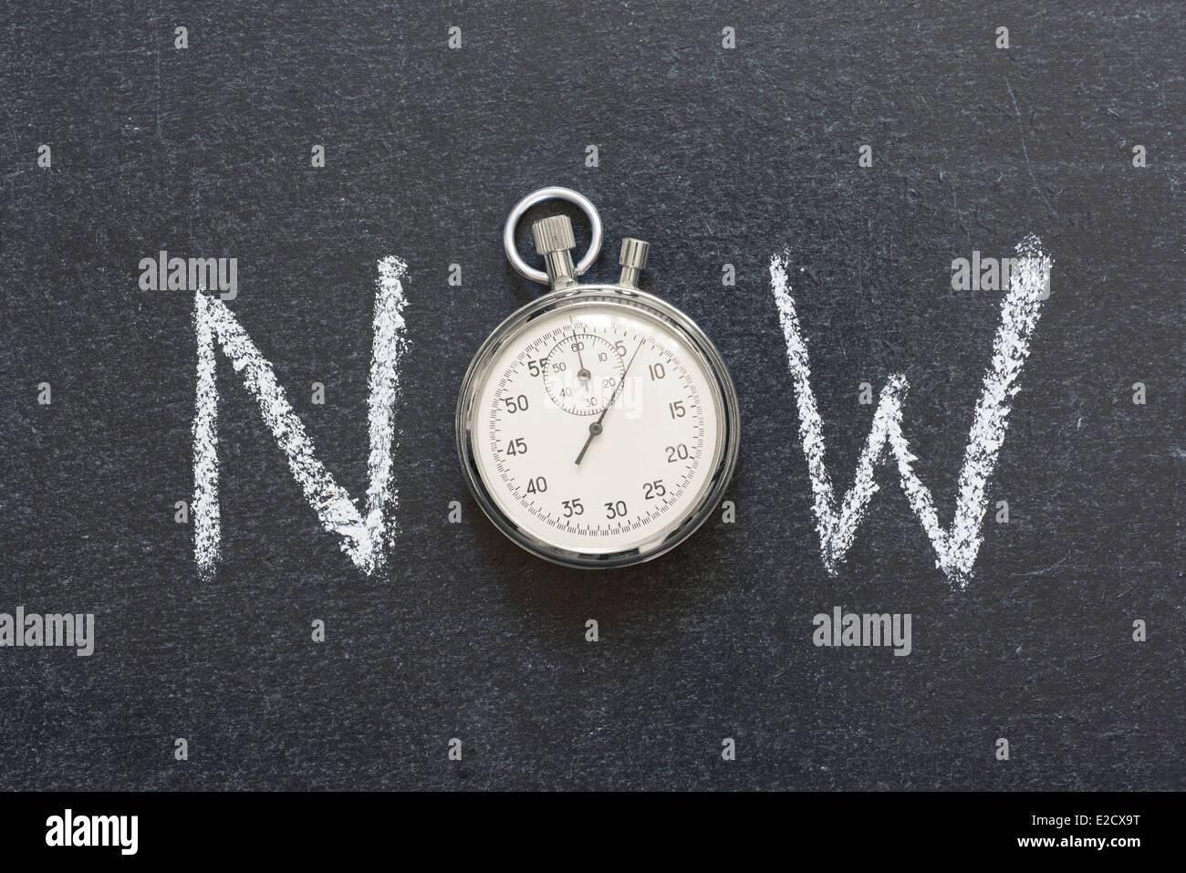 Ahora concepto manuscrito en pizarra con vintage cronómetro exacto utilizado en lugar de O Imagen De Stock
