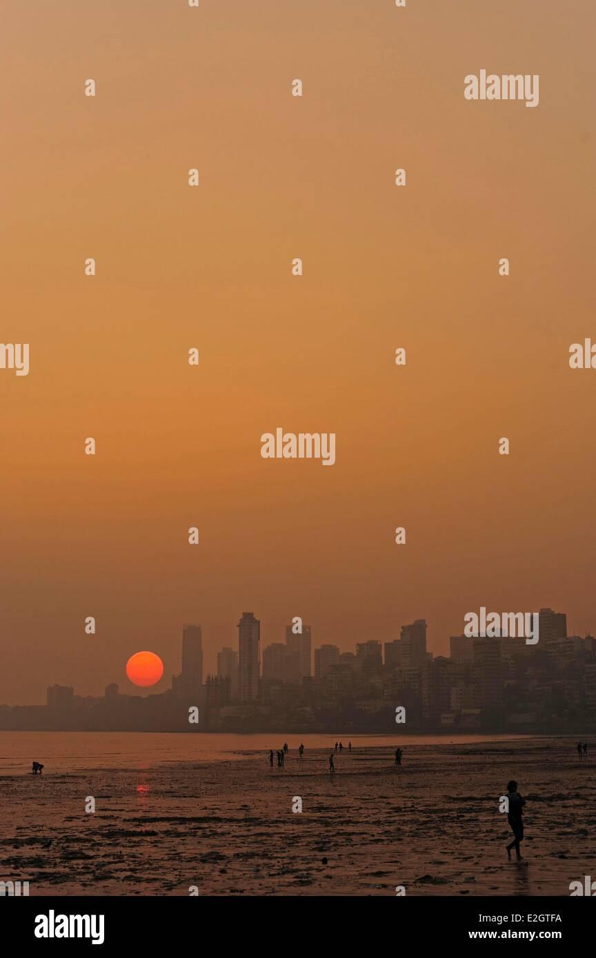 Estado de Maharashtra, India Mumbai Chowpatty beach atardecer con el sol rojo bajando en el horizonte Imagen De Stock