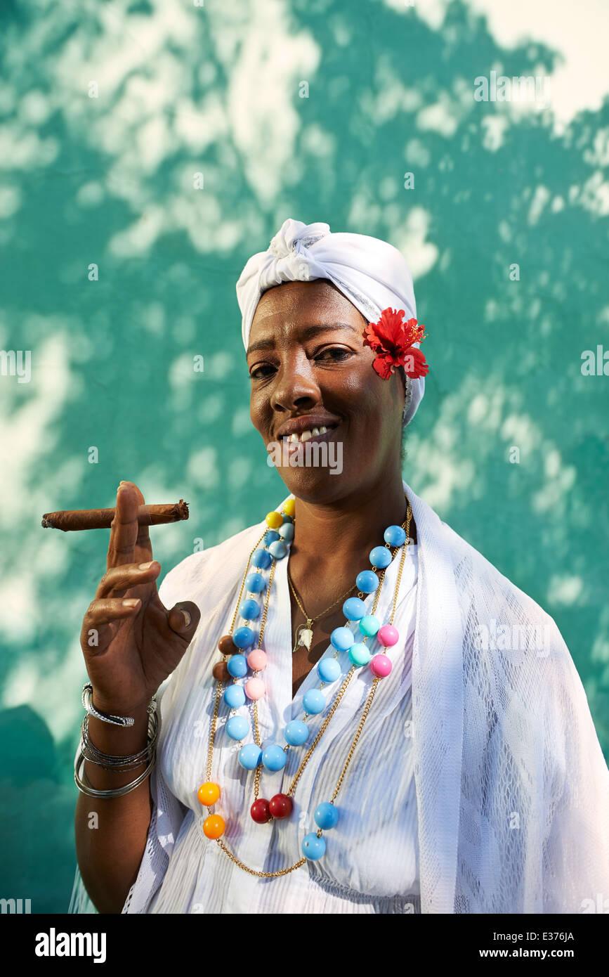 Retrato de mujer cubana africanos fumar cigarro Cohiba y mirando a la cámara sonriendo Imagen De Stock