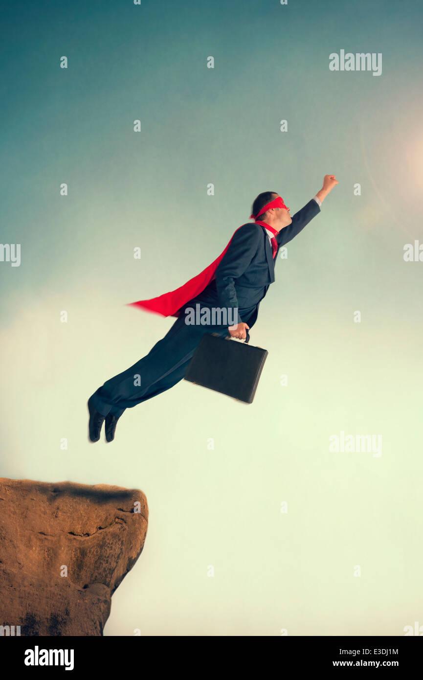 Superhéroe empresario despegar al vuelo desde un acantilado ledge vistiendo una capa y máscara Foto de stock