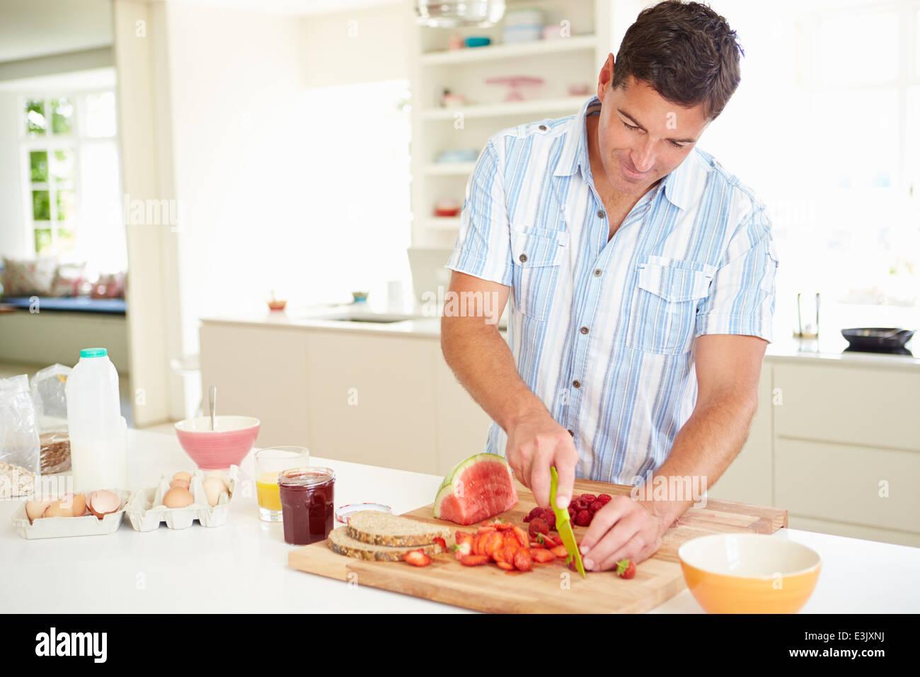 El hombre prepara desayuno saludable en la cocina Imagen De Stock