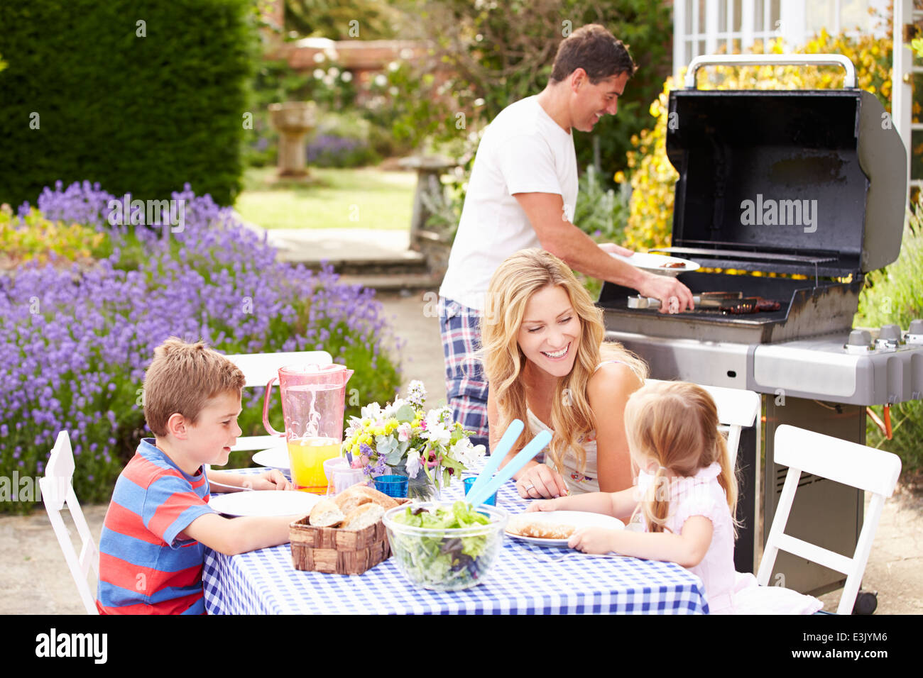 Familia disfrutando al aire libre en el Jardín Barbacoa Imagen De Stock