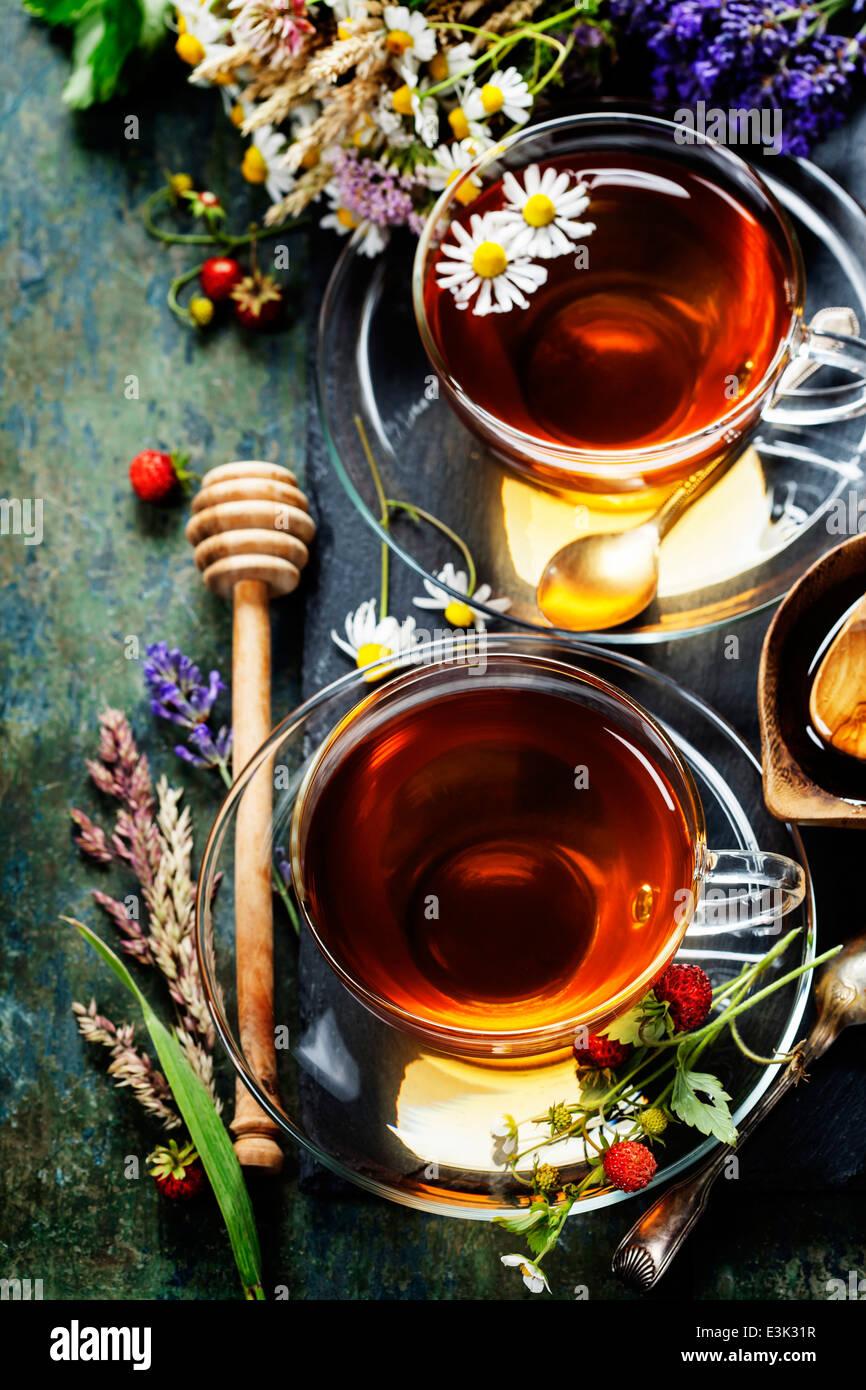 Té de hierbas con miel, Wild Berry y flores sobre fondo de madera Foto de stock