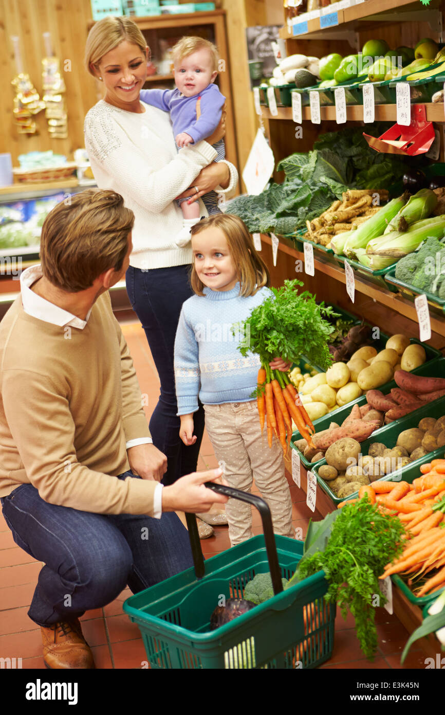 Familia eligiendo las hortalizas frescas en Farm shop Imagen De Stock