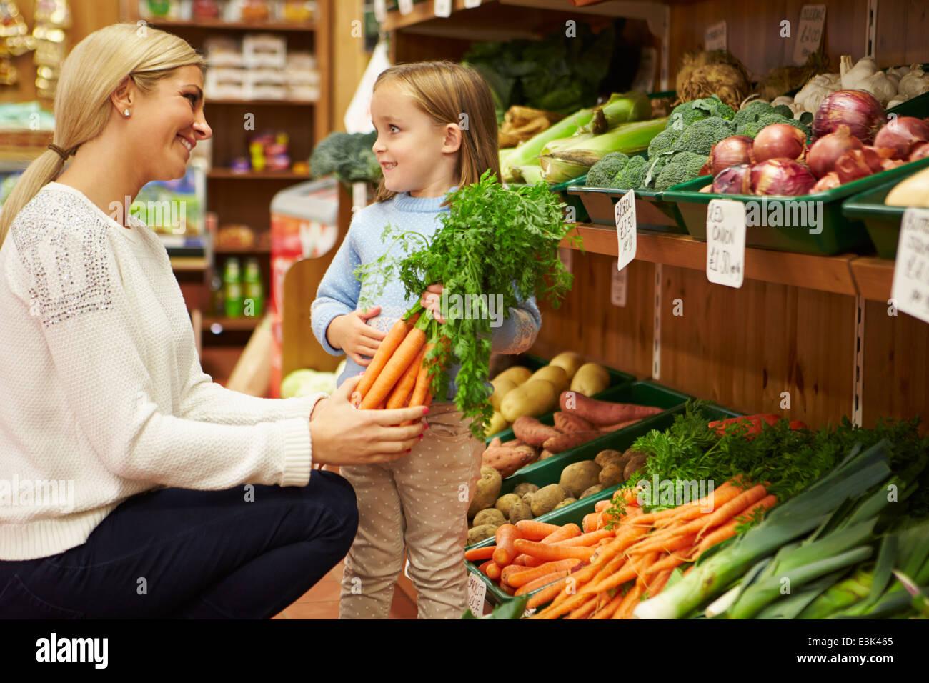 Madre e hija, en la elección de las hortalizas frescas en Farm shop Imagen De Stock