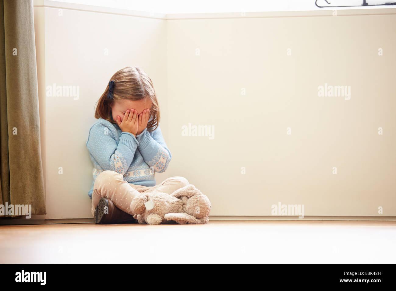 Infeliz niña sentada en el suelo en casa de esquina Imagen De Stock