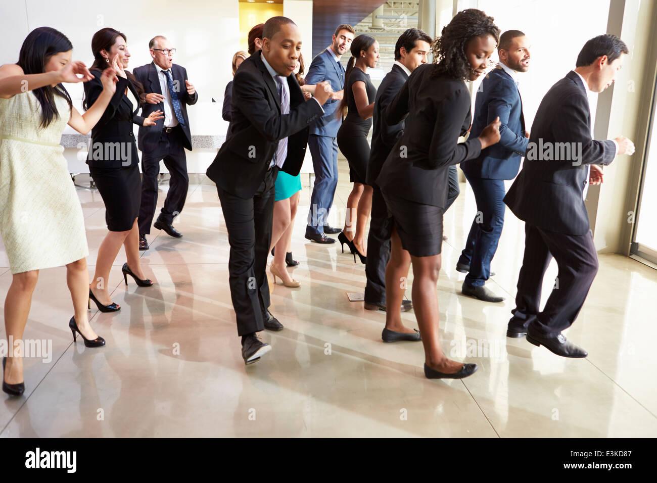Empresarios y empresarias bailando en el vestíbulo de la oficina Imagen De Stock