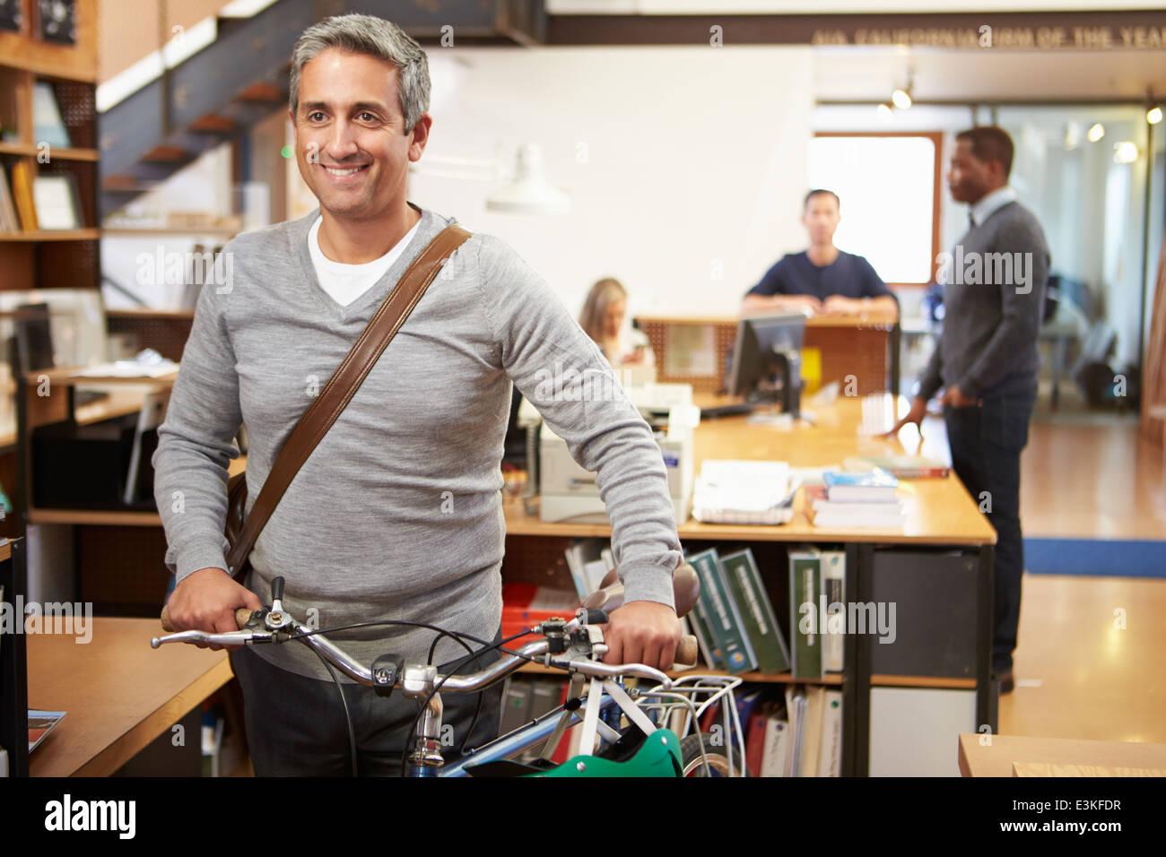 El arquitecto llega a su trabajo en bicicleta empujándolo a través de Office Imagen De Stock