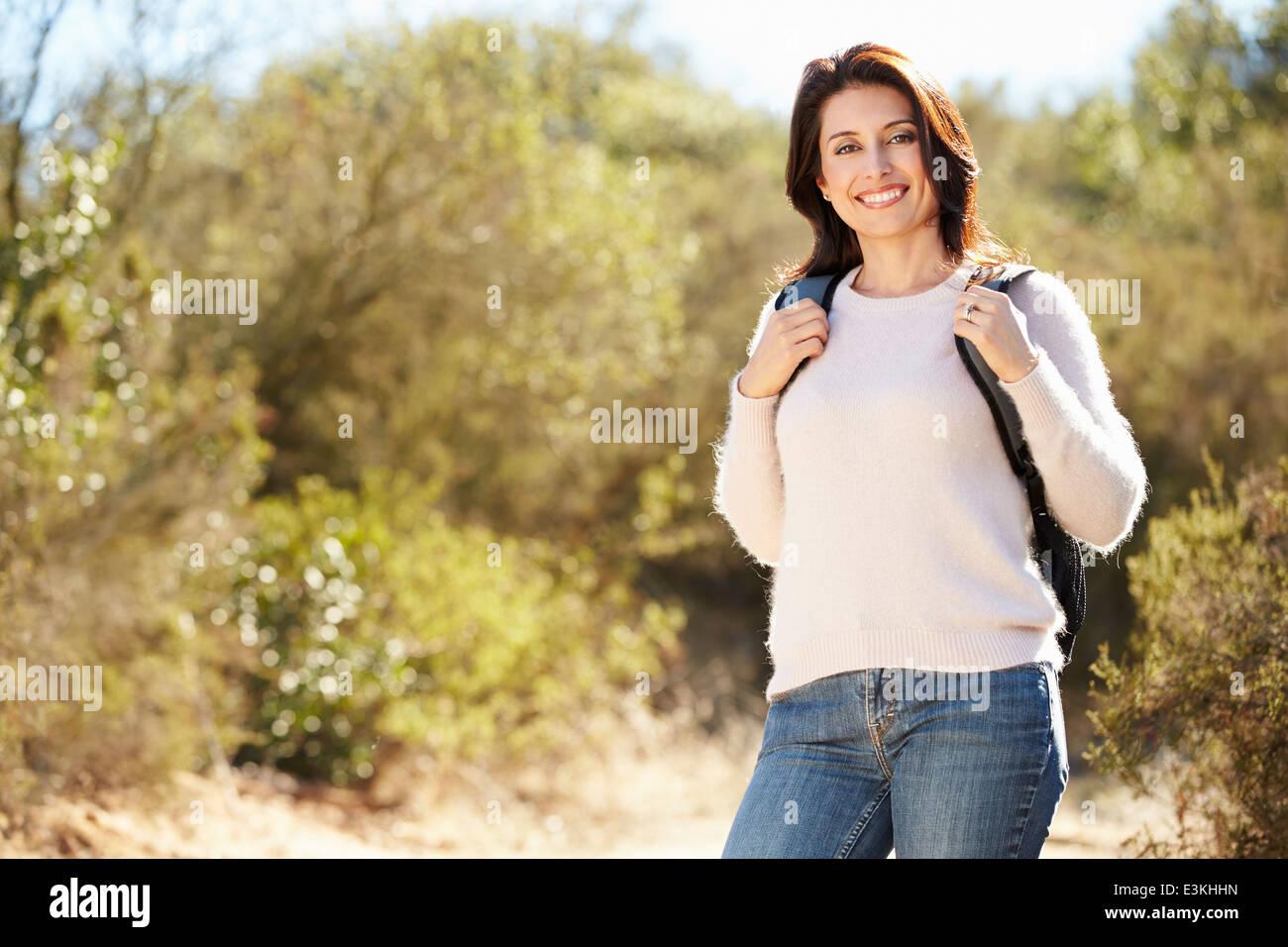 Retrato de mujer en medio del campo, vistiendo mochila de senderismo Imagen De Stock