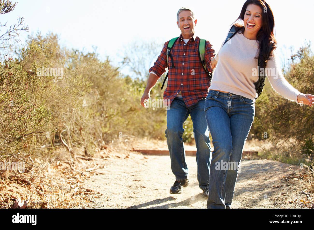Par de senderismo en campo portando mochilas Foto de stock