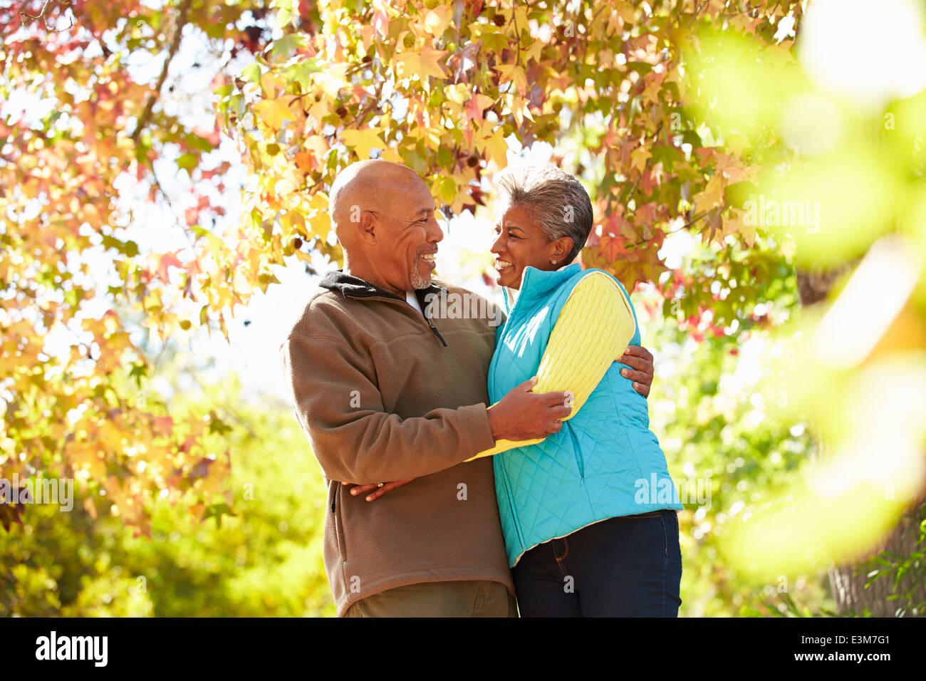 Las parejas ancianas caminando a través del bosque de Otoño Imagen De Stock