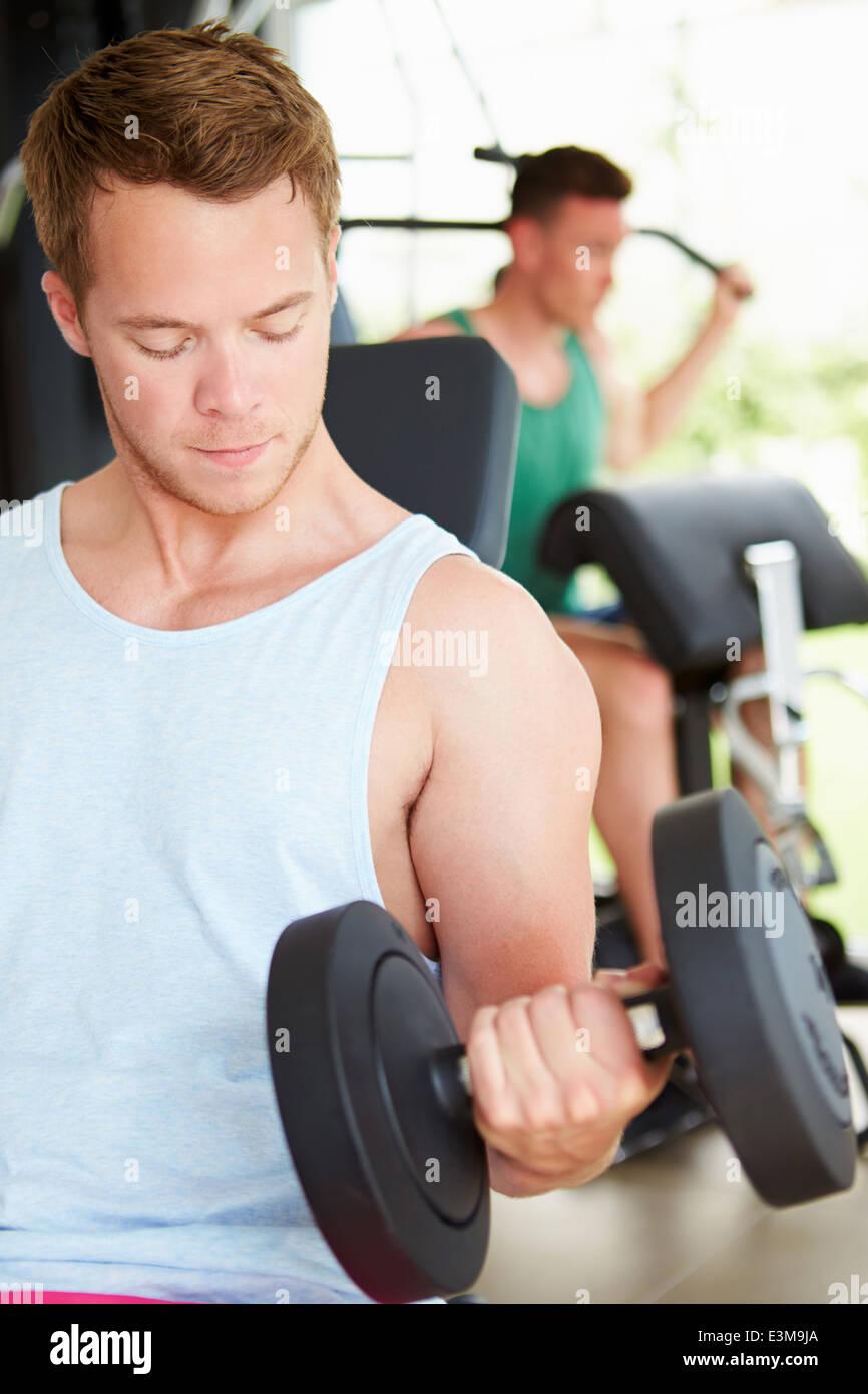 Dos hombres jóvenes capacitación en gimnasio con pesas Imagen De Stock