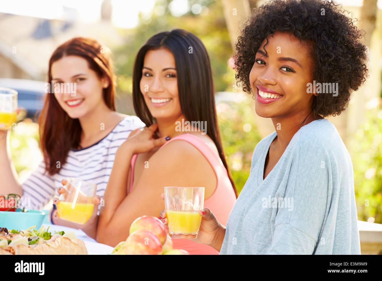 Tres Amigas disfrutando de comida en la fiesta al aire libre Imagen De Stock