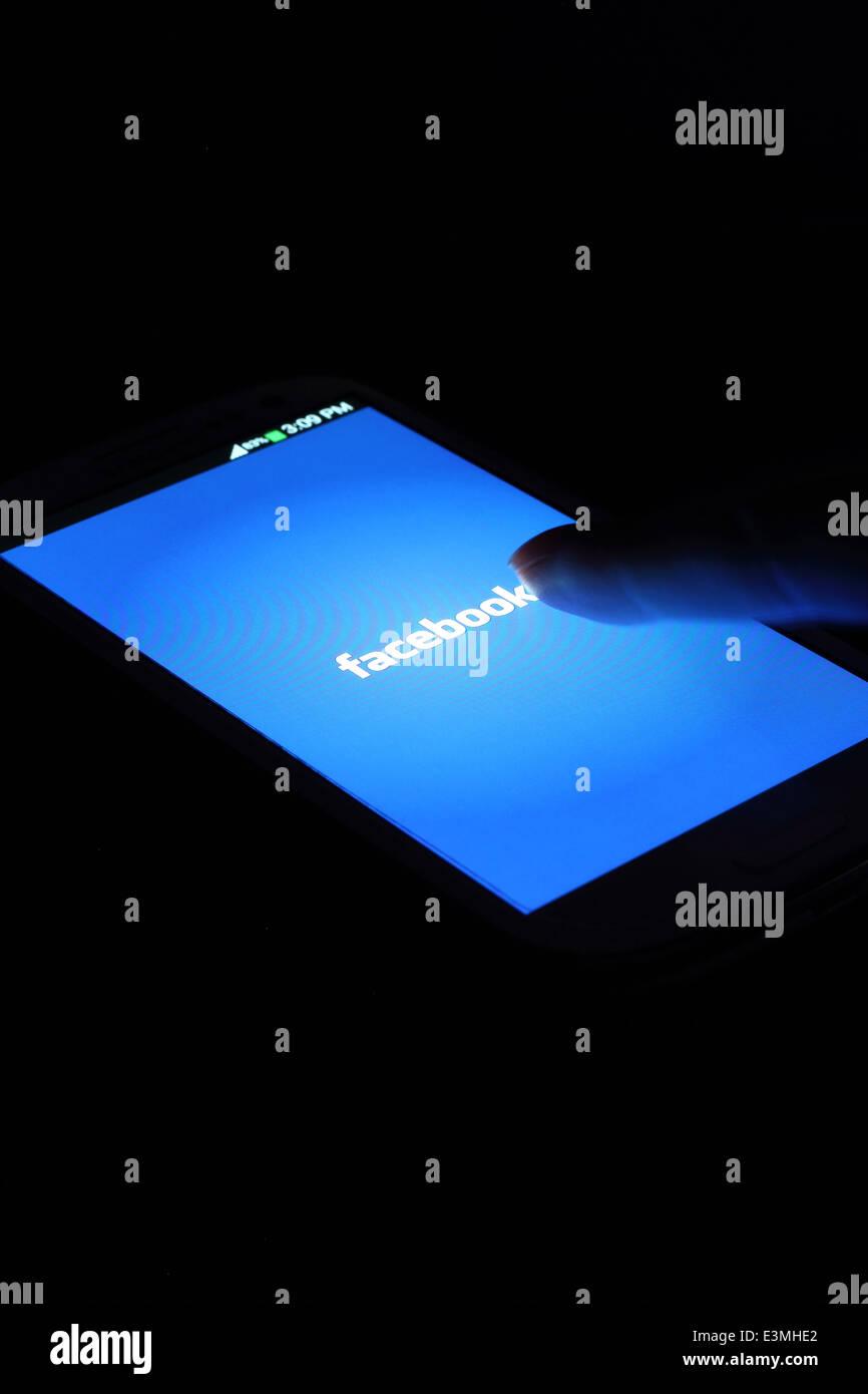 Aplicación de Facebook en la pantalla del teléfono inteligente. Facebook es la red social más grande Imagen De Stock