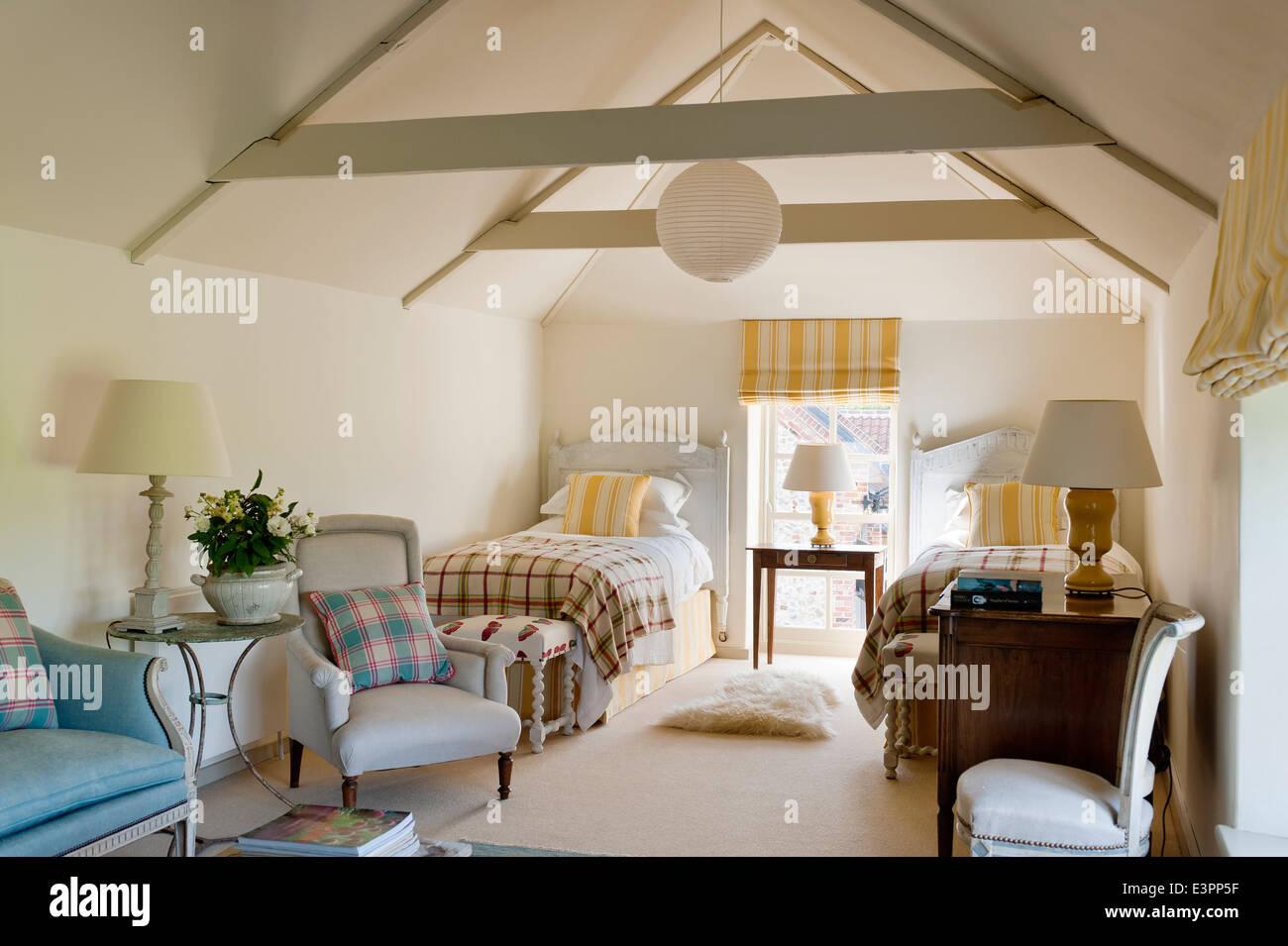 Buhardilla habitación doble con techos de madera, persianas coincidente con franjas amarillas y cojines y sillones Imagen De Stock