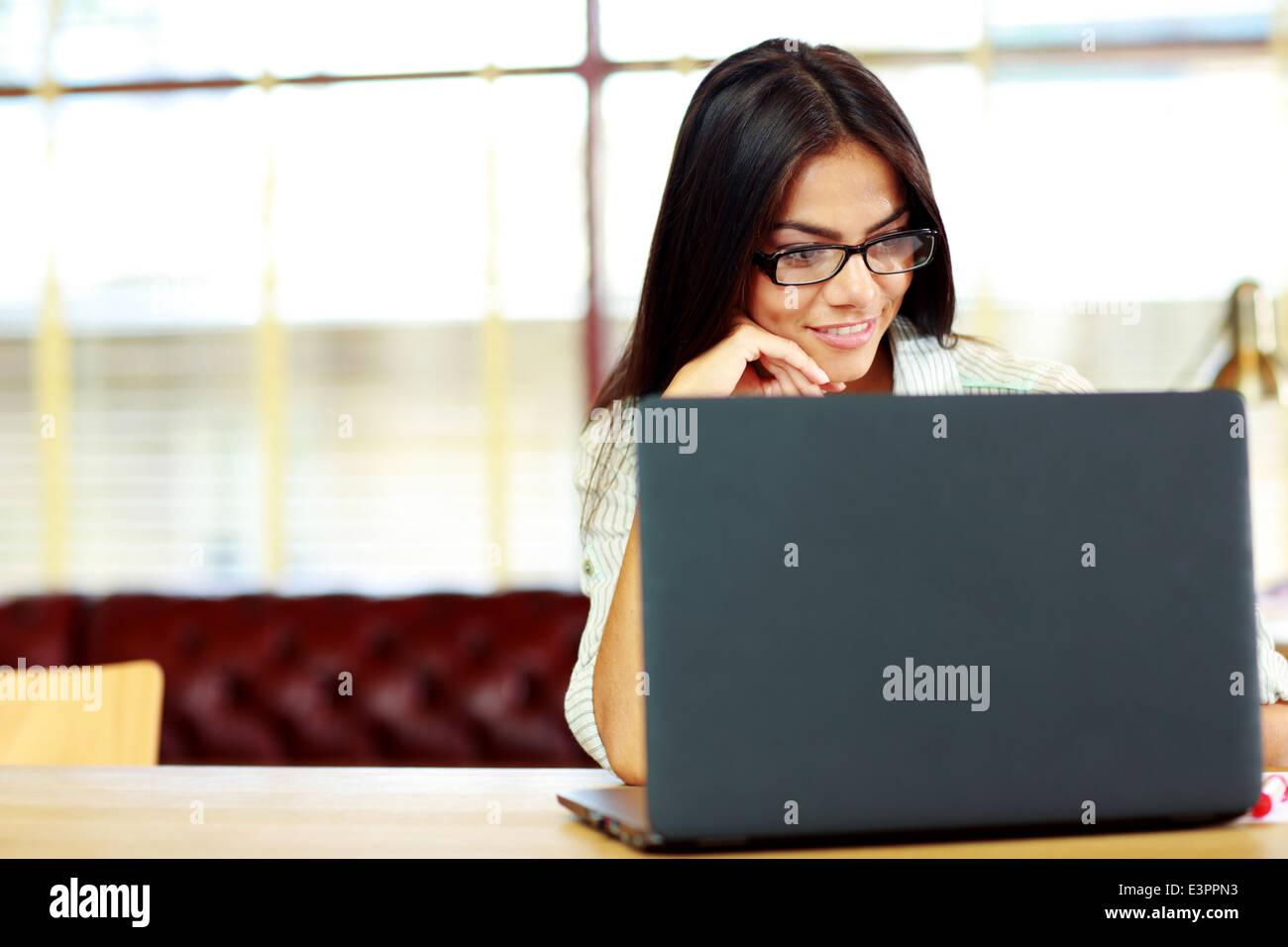 La empresaria feliz trabajando en el portátil en la oficina Imagen De Stock