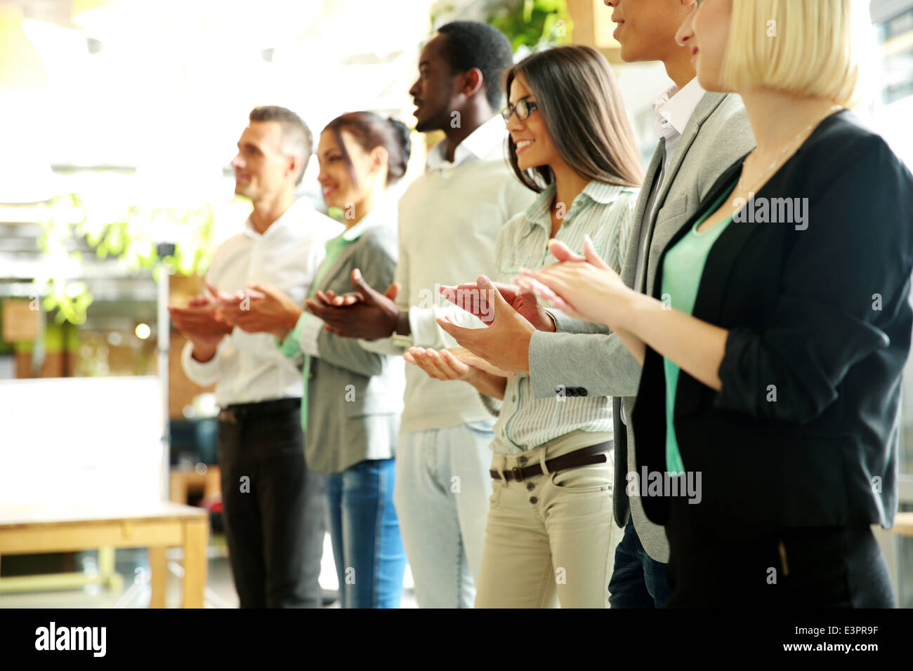 Grupo de alegre equipo empresarial aplaudiendo Foto de stock