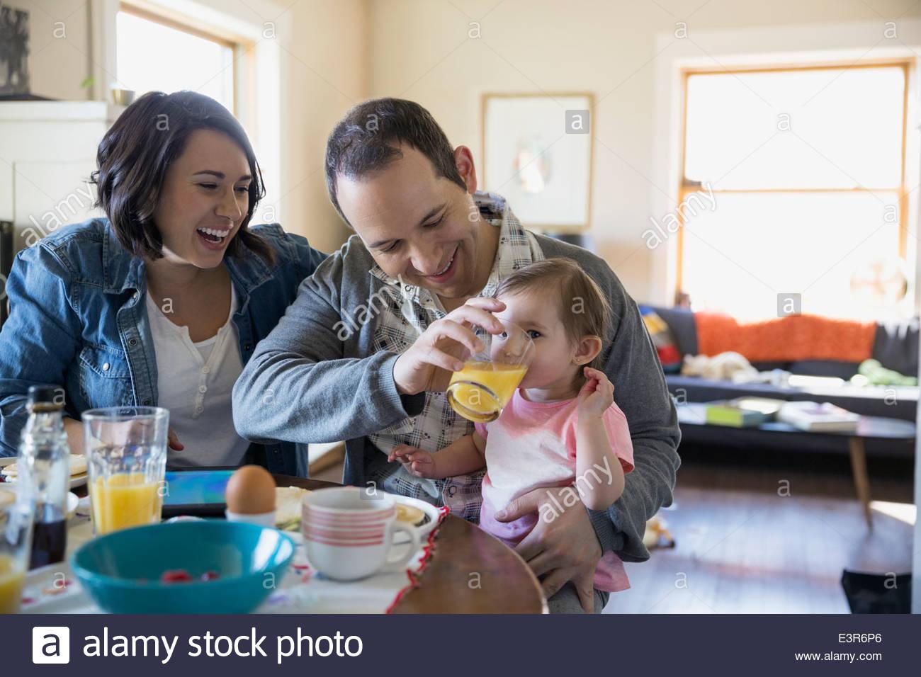 Joven familia disfrutando del desayuno en la mesa de comedor Imagen De Stock