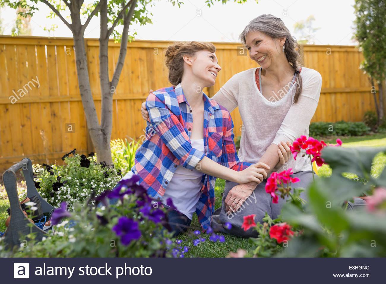Afectuoso, madre e hija de plantar flores en el jardín Imagen De Stock