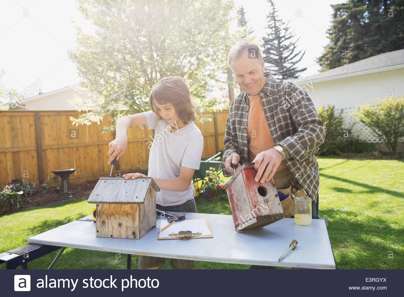 Abuelo y nieto hacer birdhouses en patio Imagen De Stock