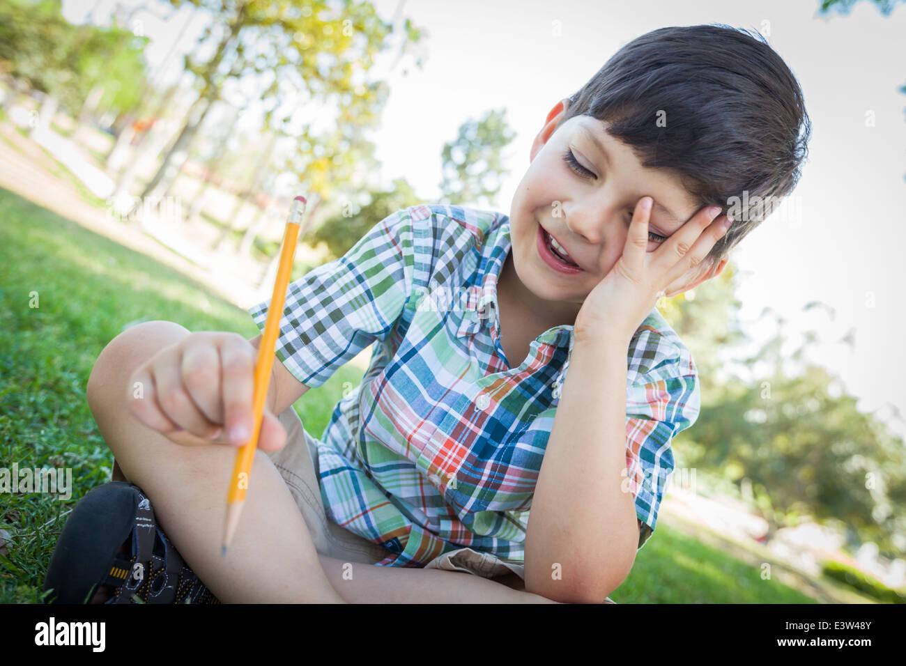 Frustrado muchacho lindo manteniendo el lápiz sobre el césped para sentarse al aire libre. Imagen De Stock