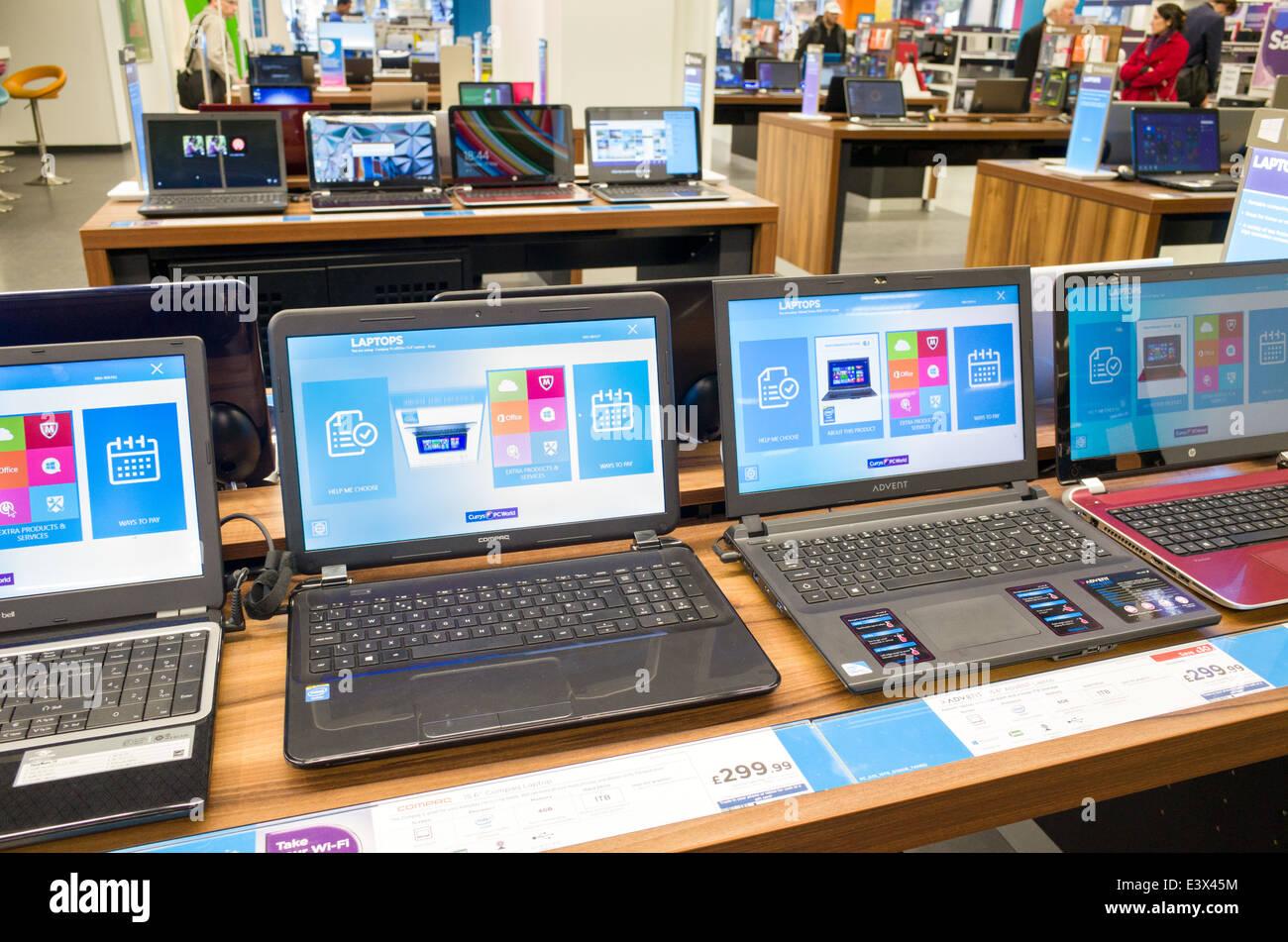 Ordenadores portátiles en pantalla en PC World, currys, Inglaterra, Reino Unido. Imagen De Stock