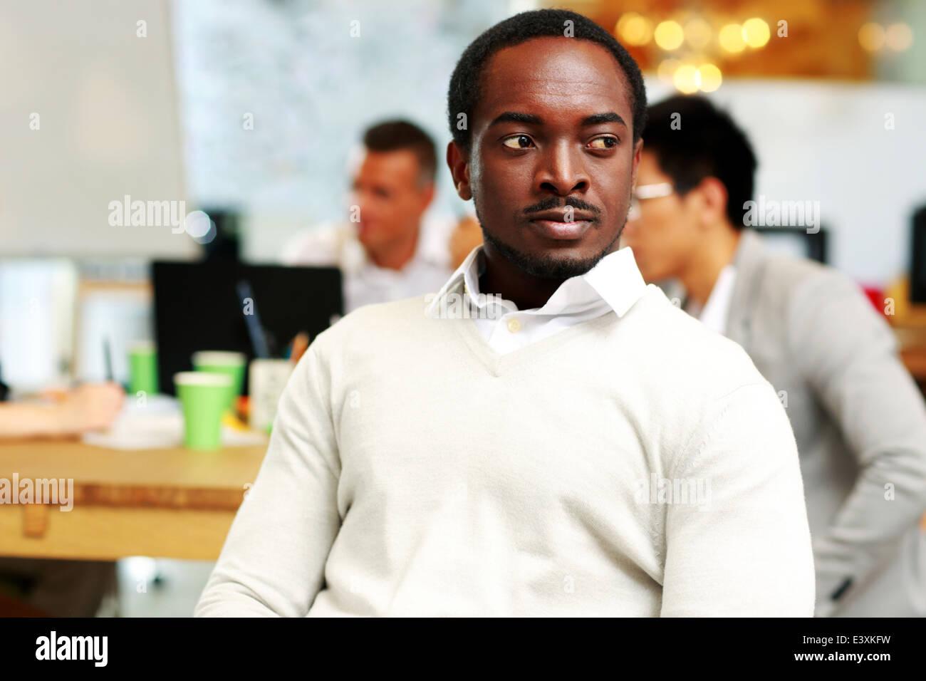 Retrato de un hombre africano pensativo mirando lejos en Office Imagen De Stock