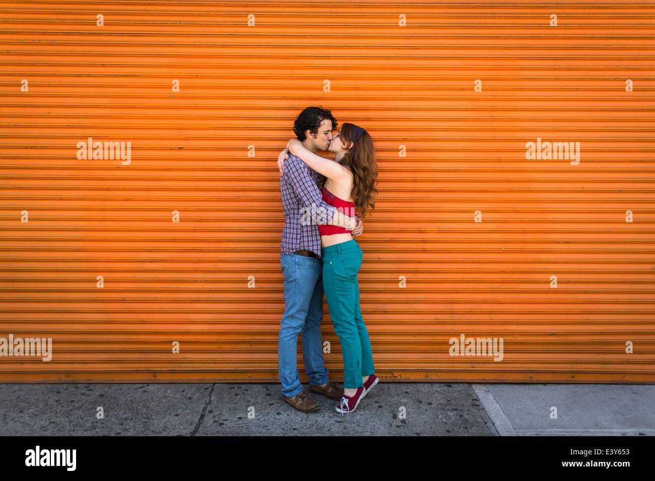 Pareja romántica besarse delante del obturador naranja Imagen De Stock