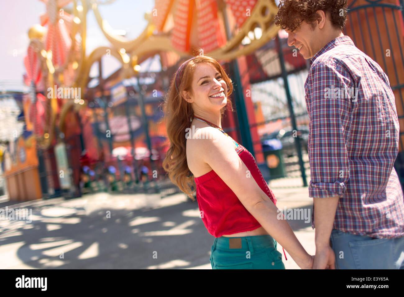 Pareja romántica cogidos de la mano en el parque de diversiones Imagen De Stock