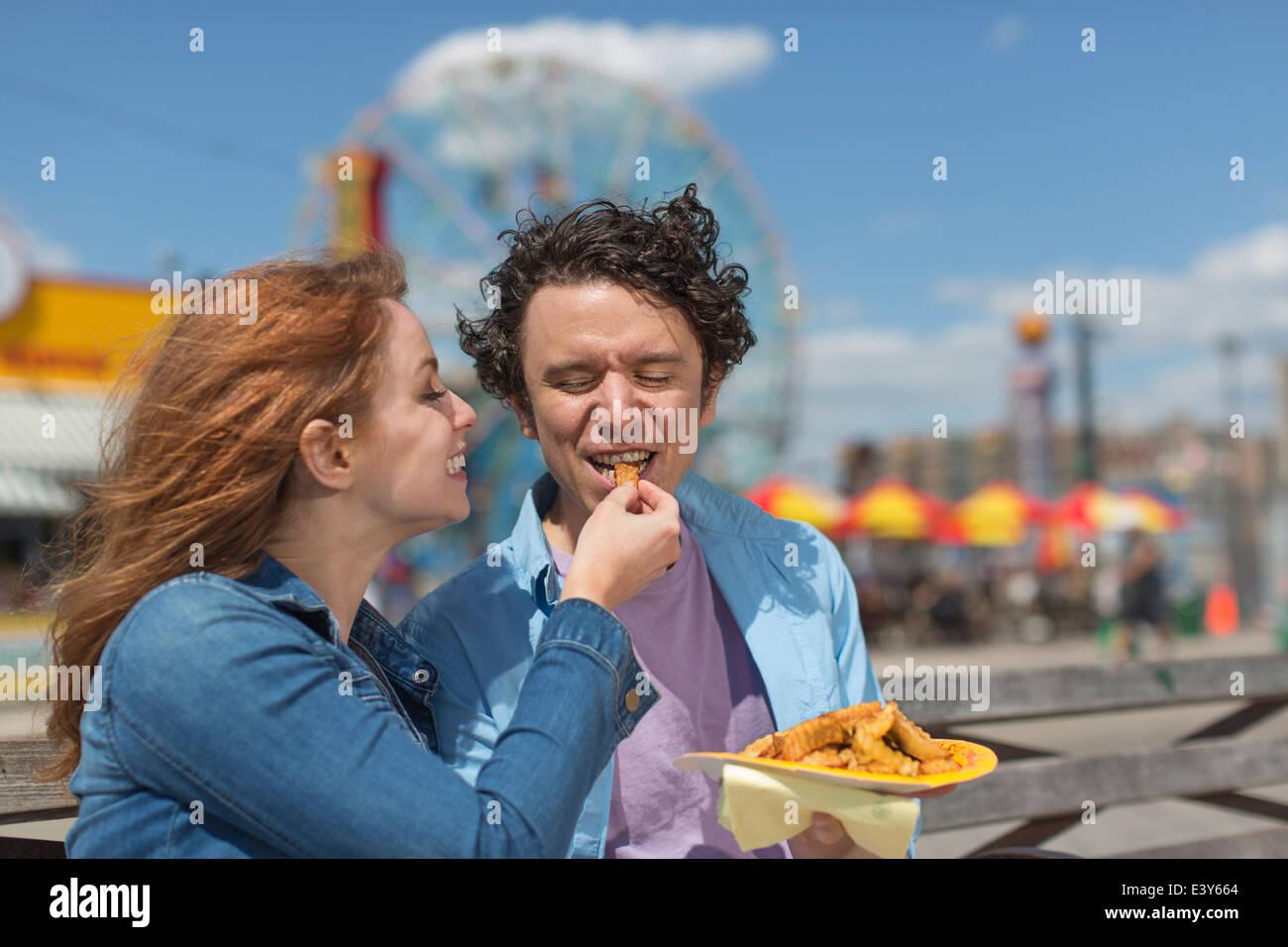 Pareja romántica de alimentación en cada otros chips en parque de diversiones Imagen De Stock