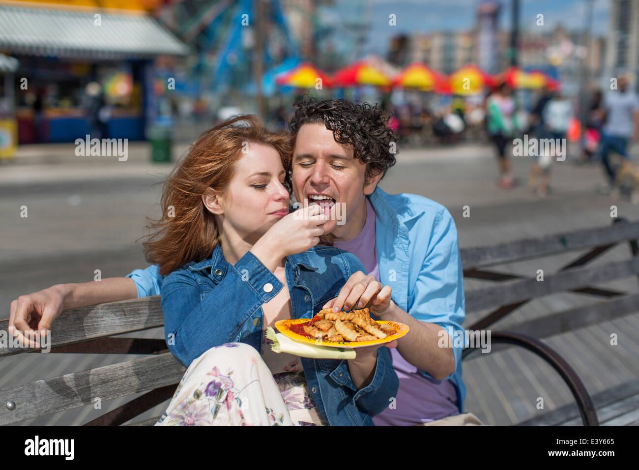 Pareja romántica comiendo patatas fritas en el parque de diversiones Imagen De Stock
