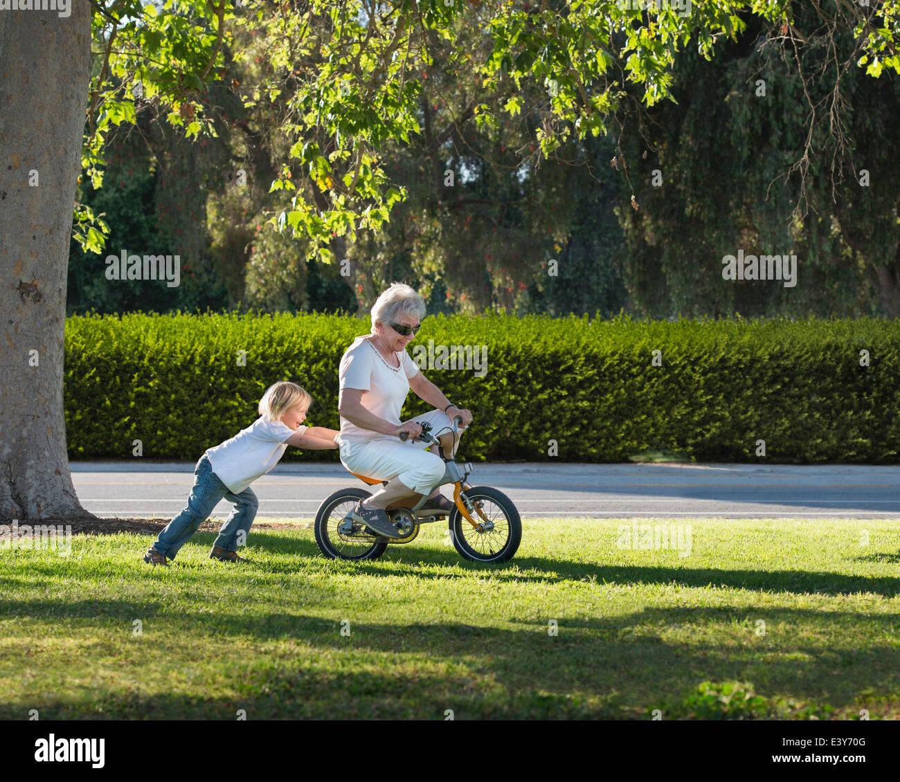 Tres años abuela niño empujando sobre ciclo en estacionamiento Imagen De Stock