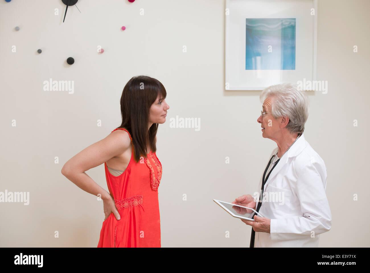 Mujer madura interrogatorio médico femenino cara a cara en el consultorio Imagen De Stock