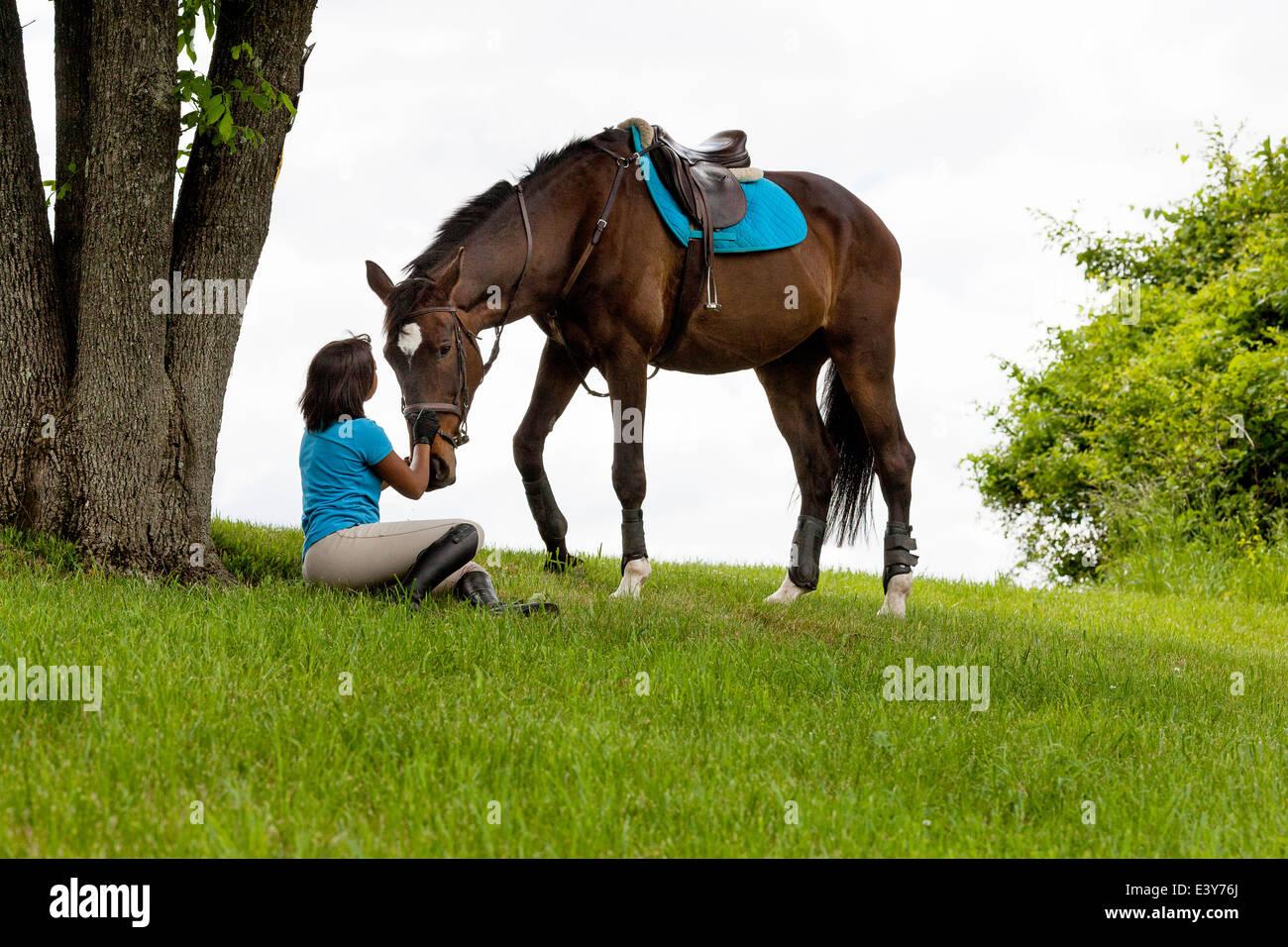 Jinete sentado junto al árbol, junto a caballo Imagen De Stock