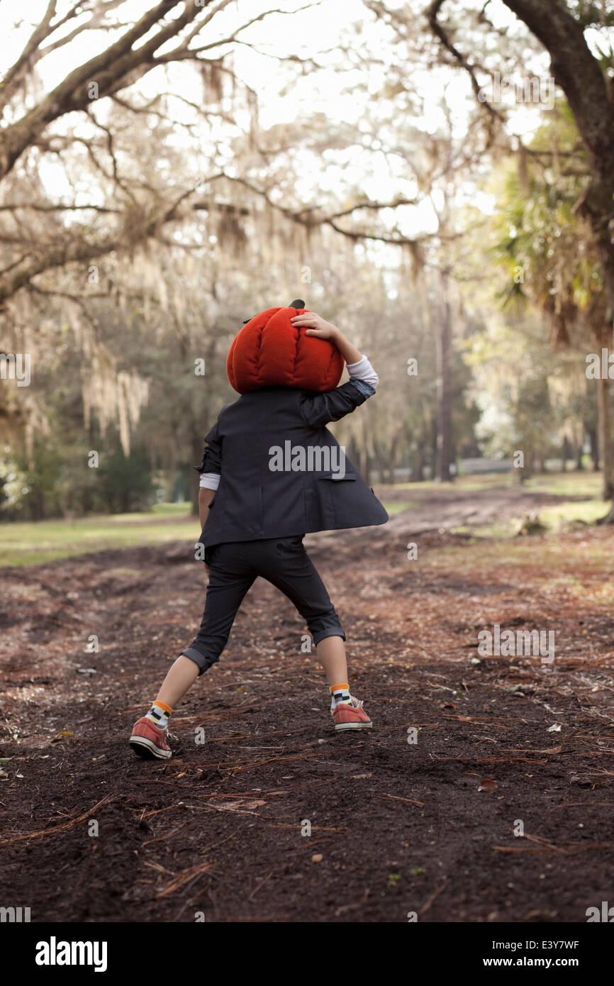 Niño corriendo en el bosque sujetando la cabeza de calabaza Imagen De Stock