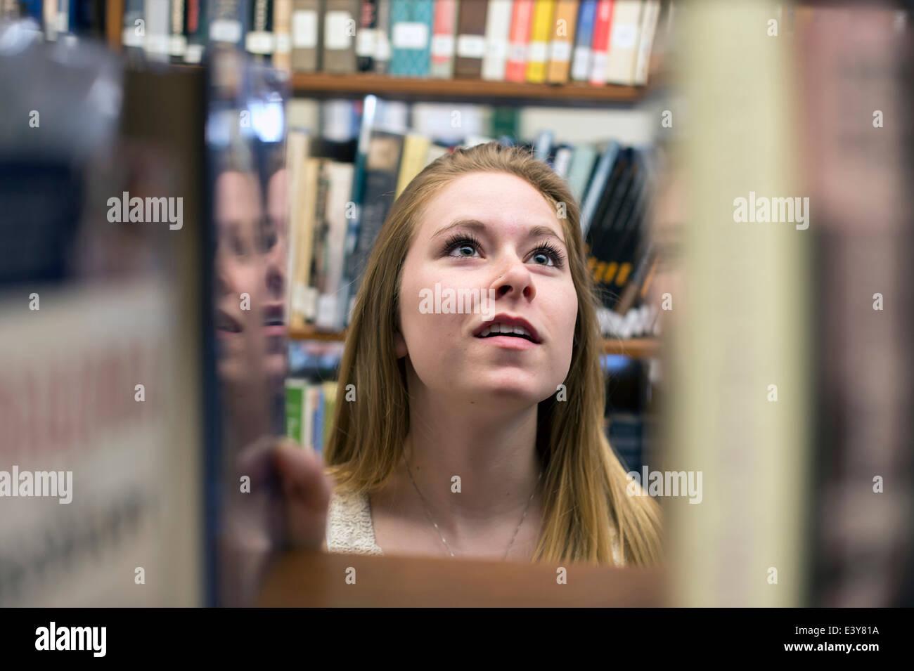Mujer joven elegir libro en la biblioteca Imagen De Stock